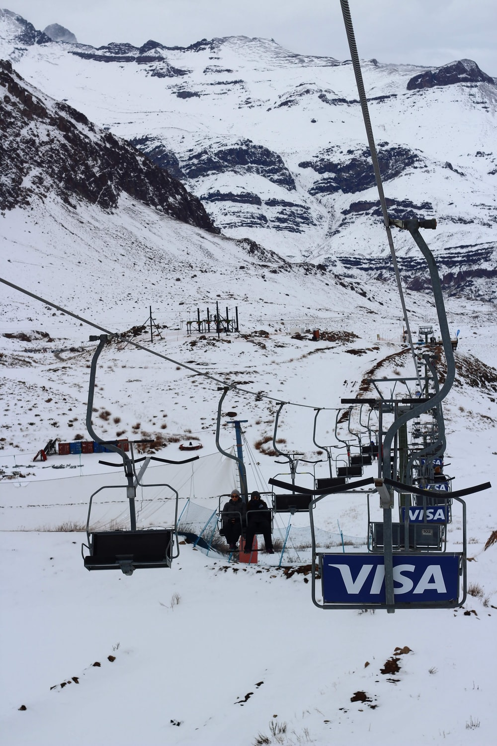 cable cars over snow covered mountain during daytime