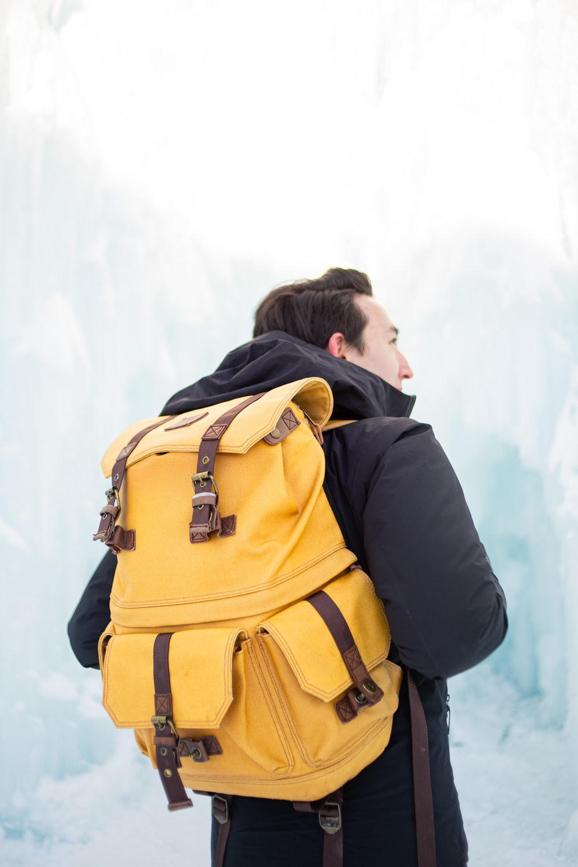 man in black jacket and brown backpack
