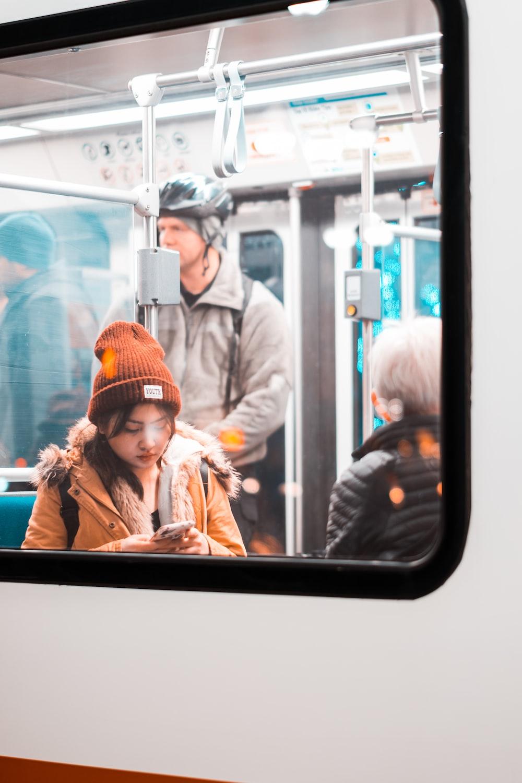 woman in brown jacket wearing orange knit cap