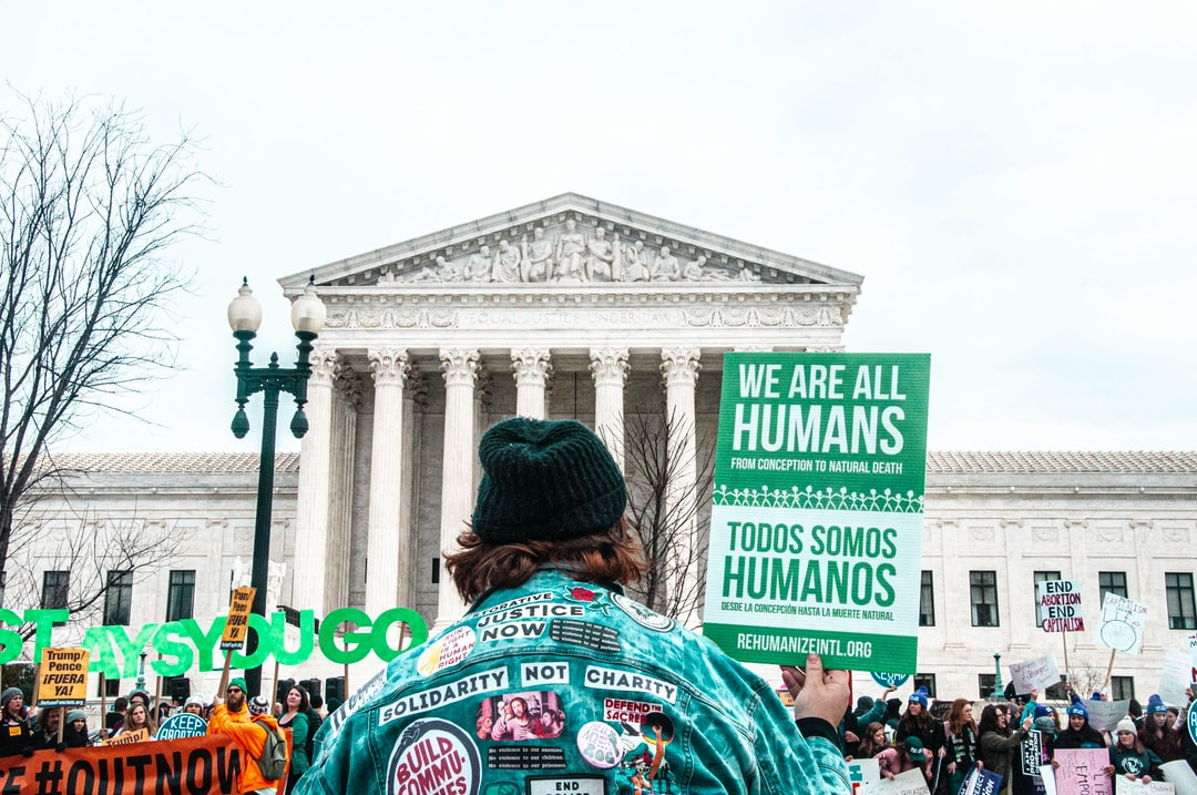 an activist holds a sign in front of the Supreme Court