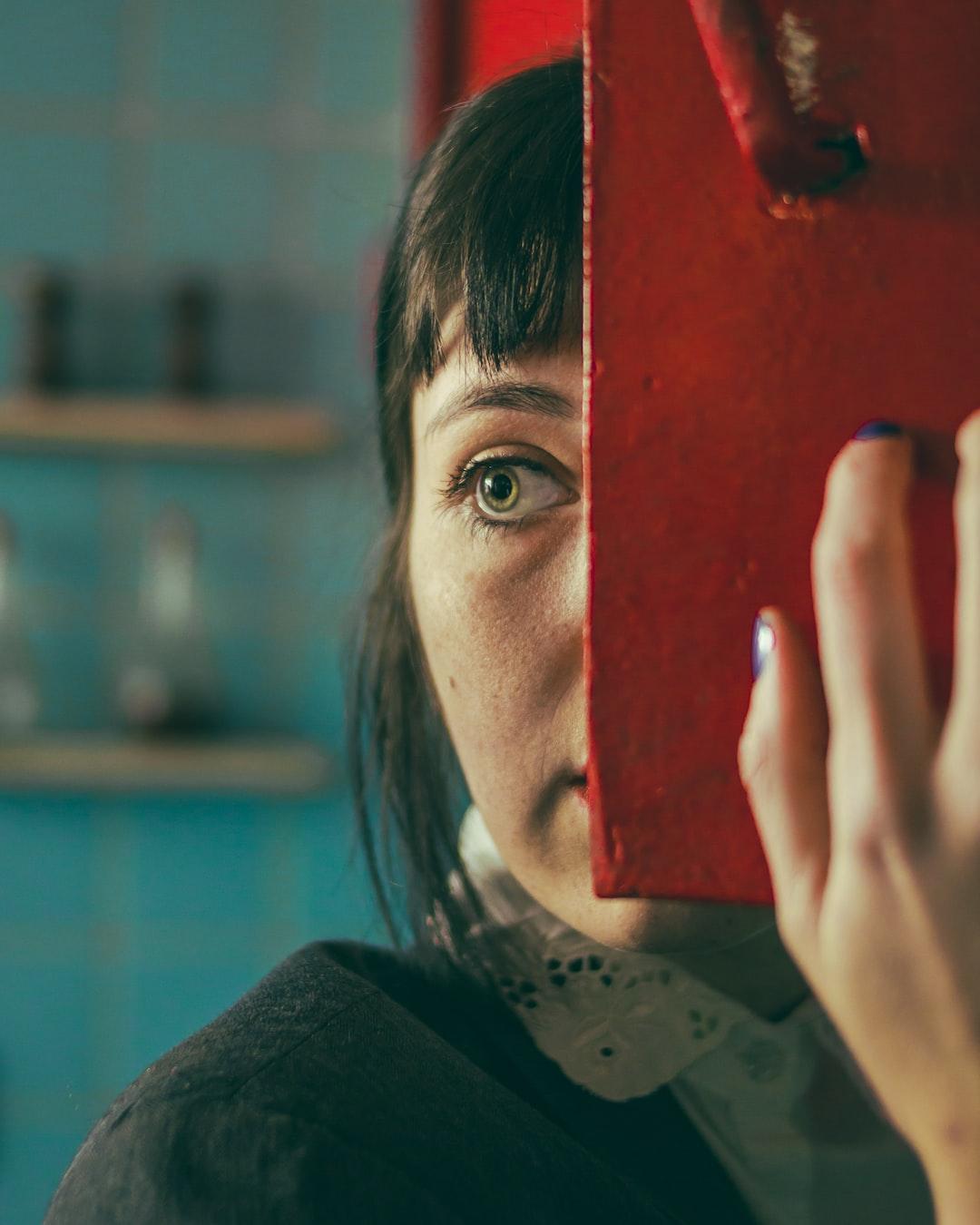 A woman hiding behind a shelf.