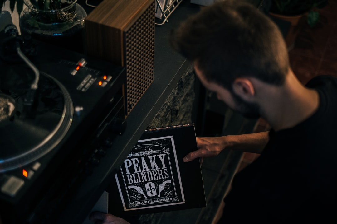 Young men taking the Peaky Blinders soundtrack album out of his vinyl collection.