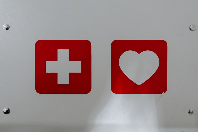 A photo of the front of a medic alert kit with a red first aid cross and a red heart on a white background.