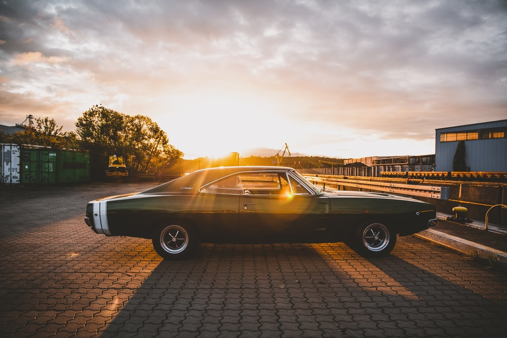 black coupe parked on brown brick floor during sunset