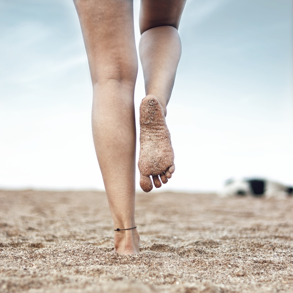 woman in brown stockings and brown boots standing on brown sand during daytime