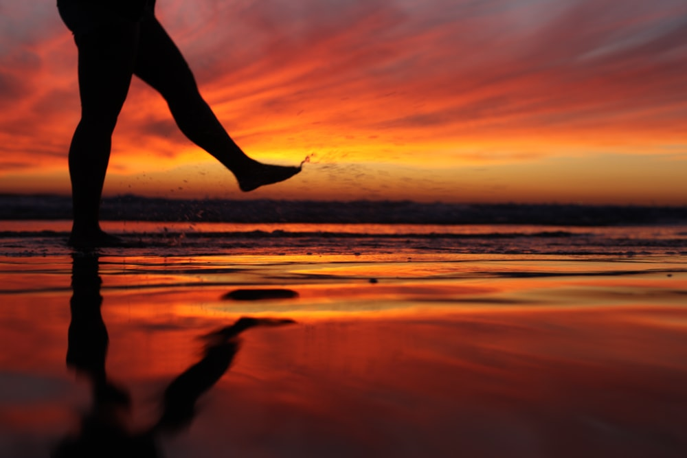 silhouette of person jumping on beach during sunset