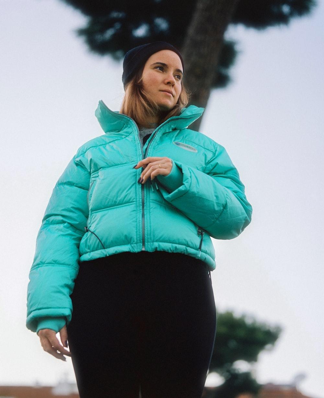 woman in teal zip up jacket and black leggings