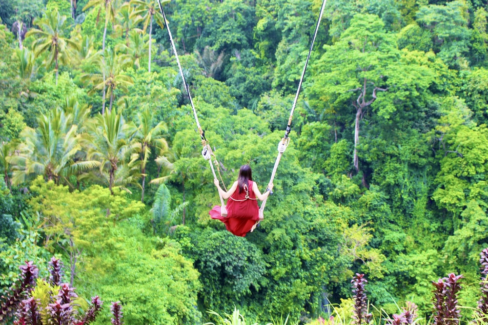 person in red jacket riding on swing