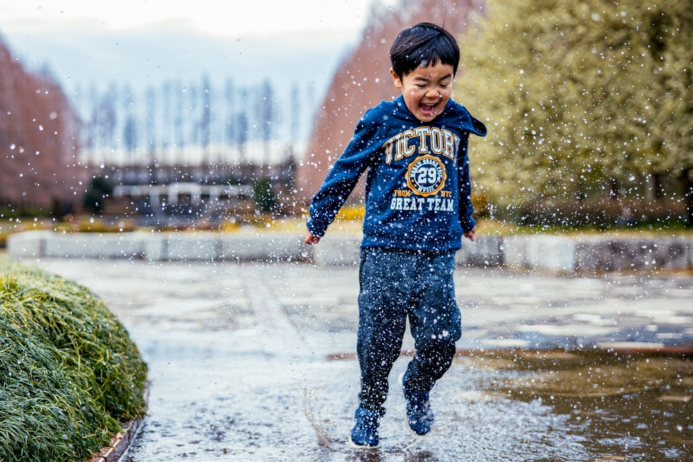 boy in blue and red hoodie standing on wet road during daytime