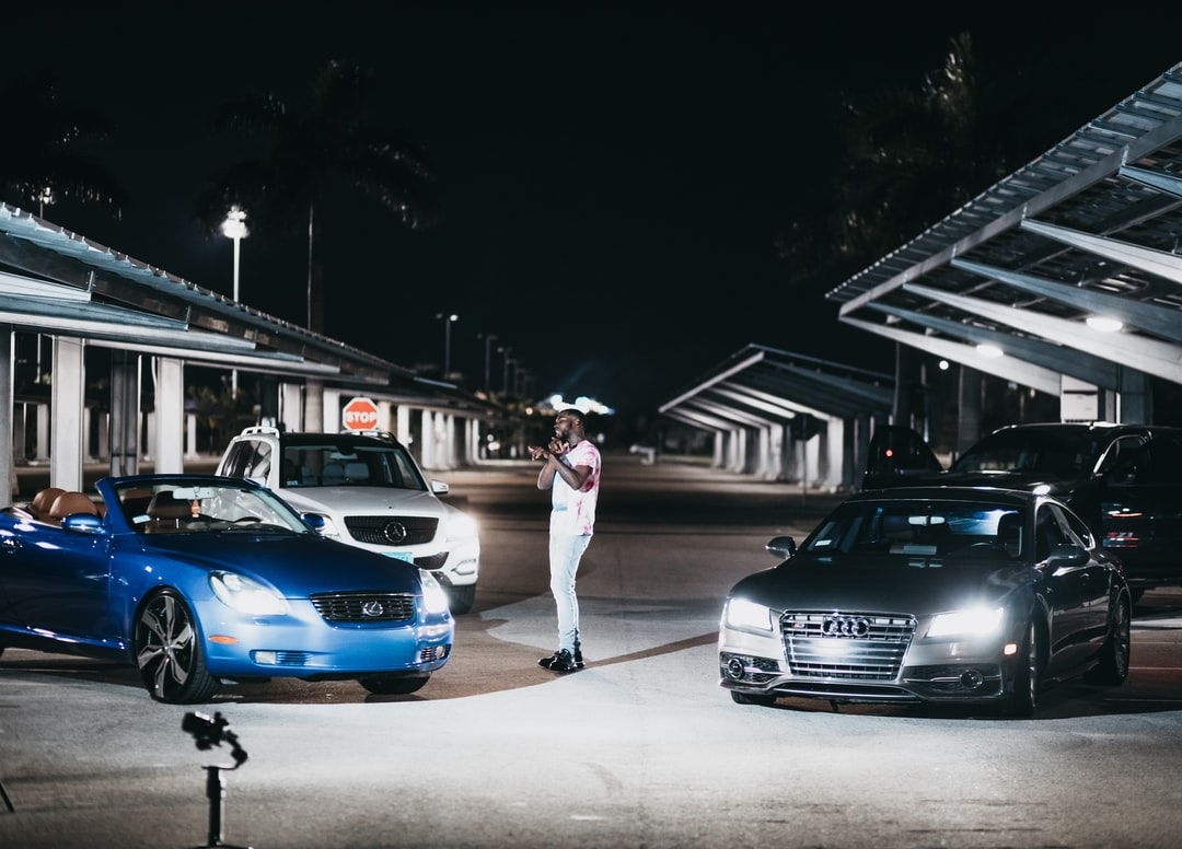 Woman In White Mini Dress Standing Beside Blue Bmw Car During Night Time - unsplash