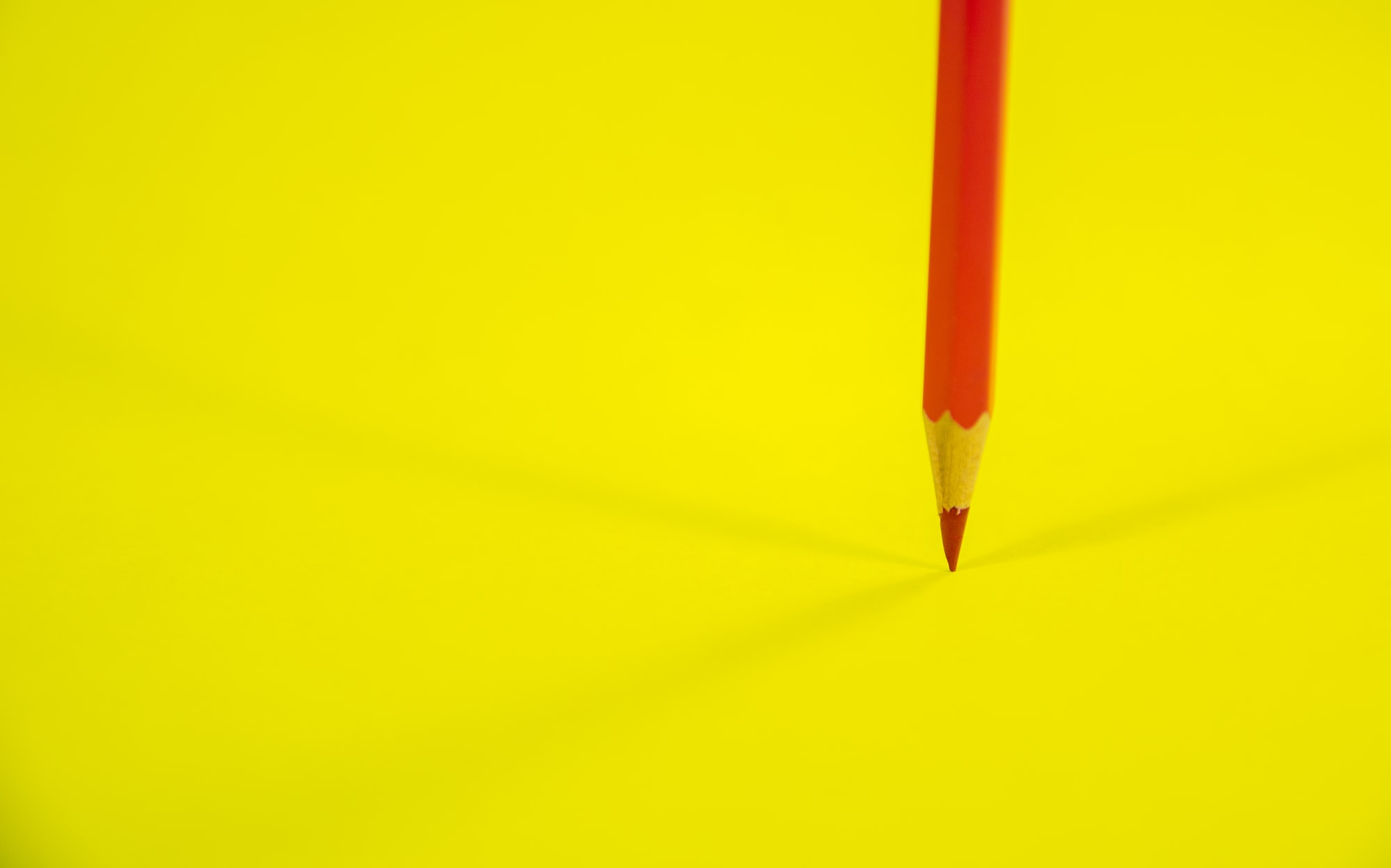 Red Color Pencil on Yellow Background