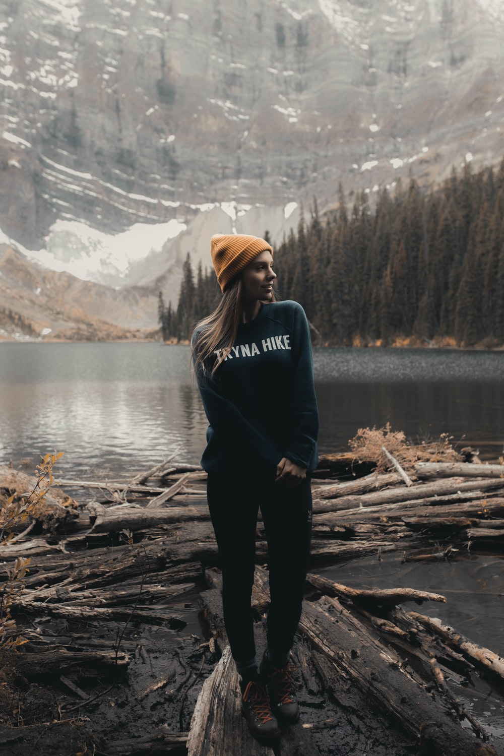 woman in black hoodie standing on brown wood log near lake during daytime
