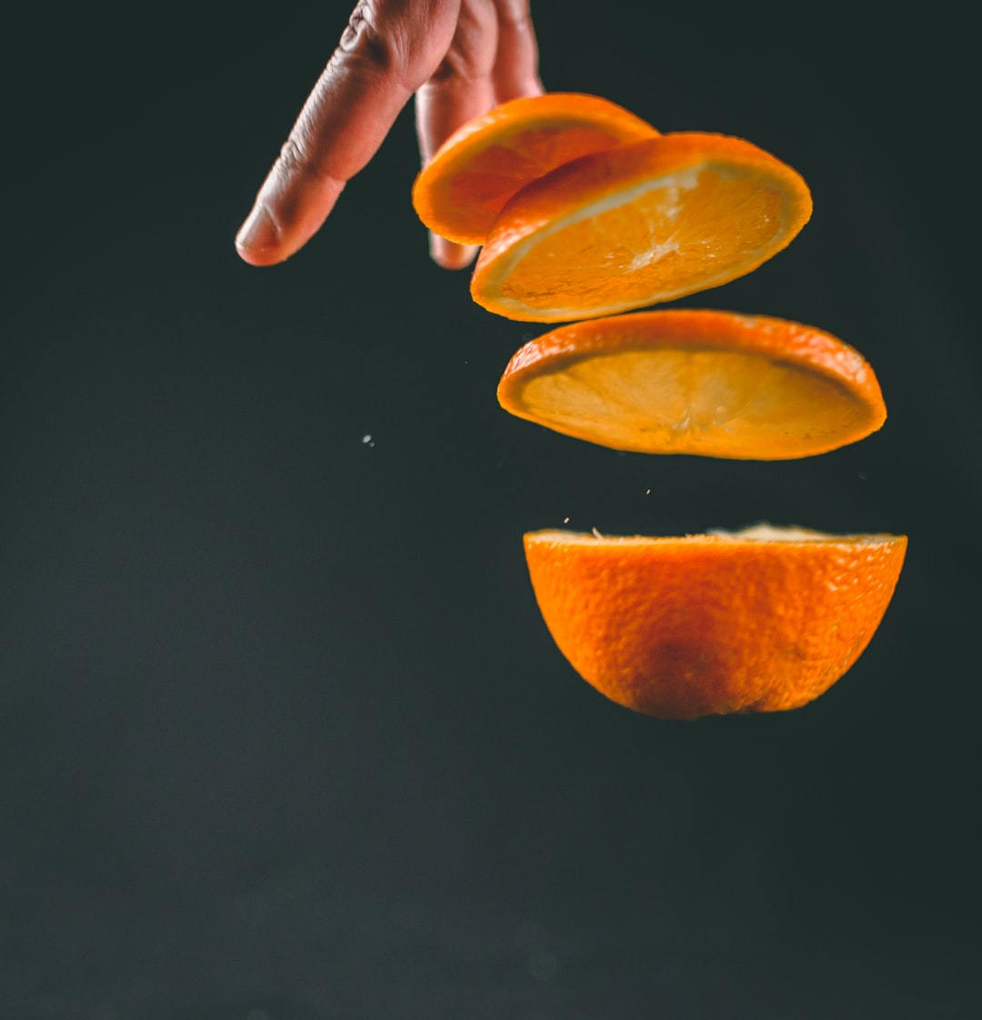 Levitating slices of orange on black background