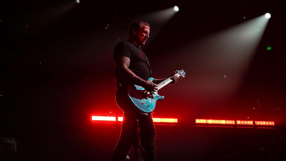 man in black t-shirt playing electric guitar