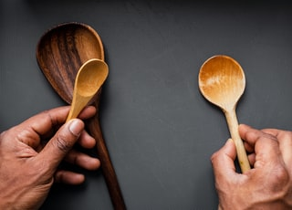 person holding brown wooden spoon