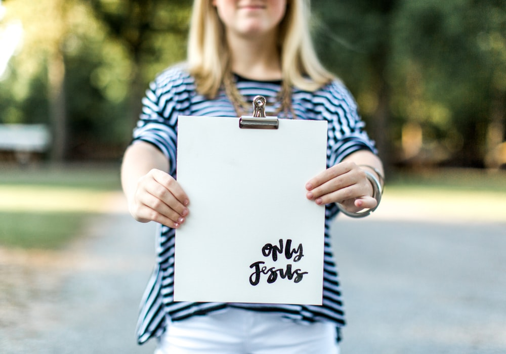 woman in blue and white long sleeve shirt holding white book