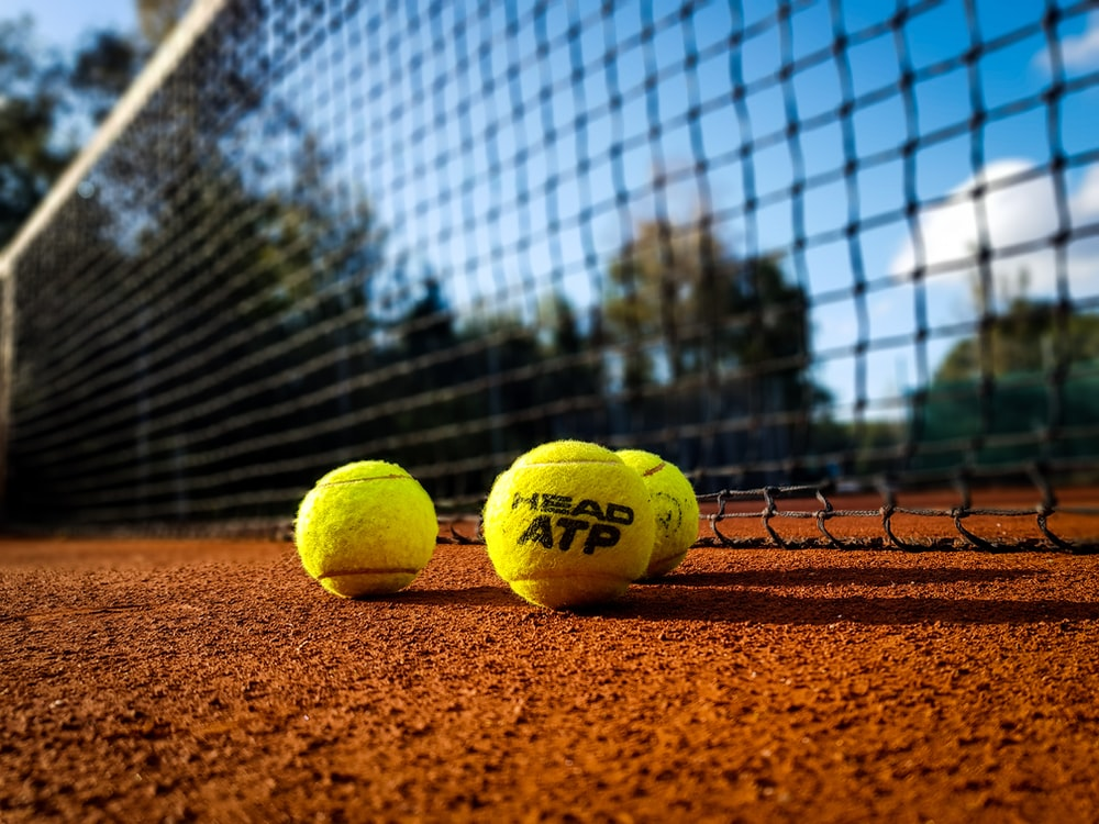 yellow tennis ball on brown sand