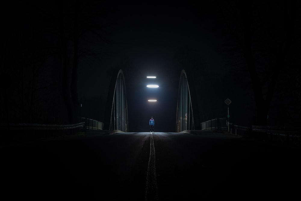 person walking on road during night time