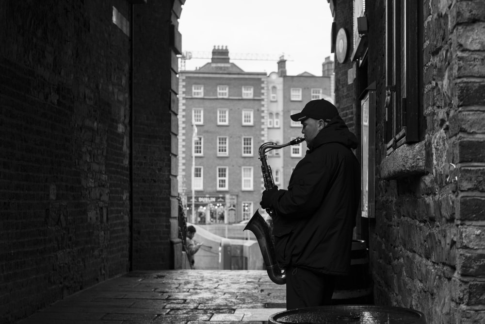 man in black jacket playing saxophone sitting on concrete bench in grayscale photography