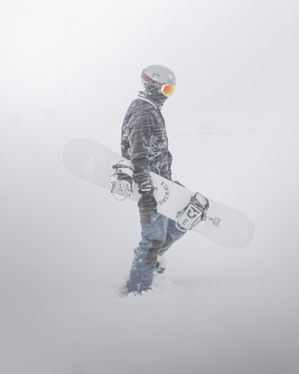 person in black and white pants and black snow shoes standing on snow covered ground during