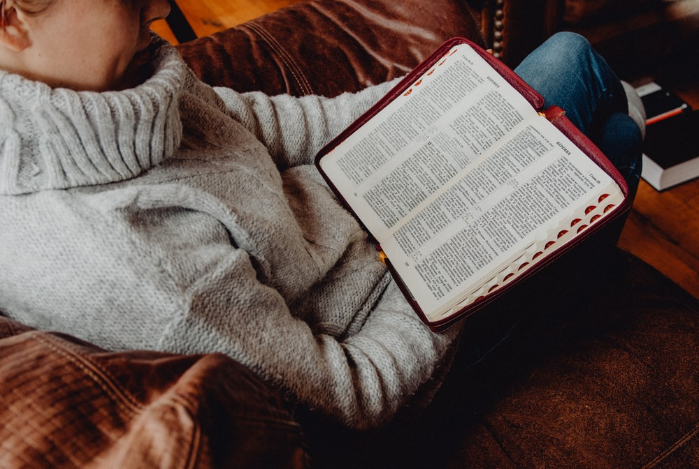 person in gray sweater reading book