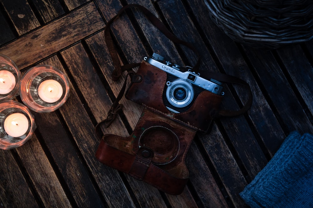 brown and silver dslr camera on brown wooden table