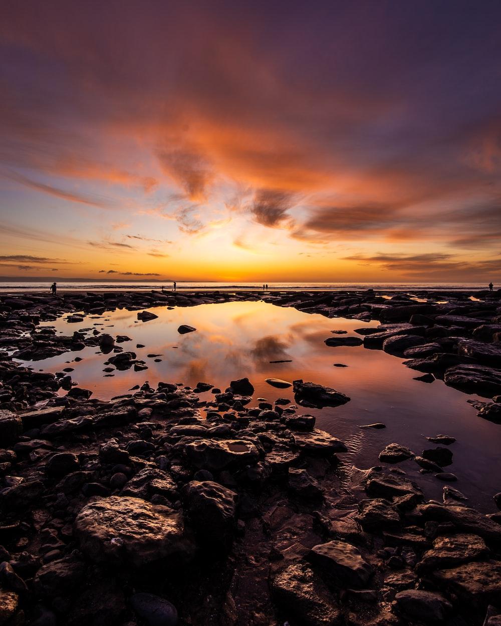 rocky shore under orange sunset