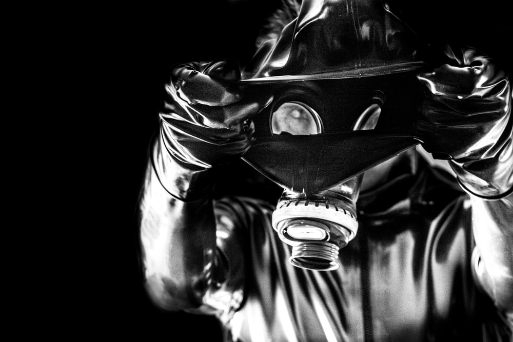 person wearing gas mask in grayscale photography