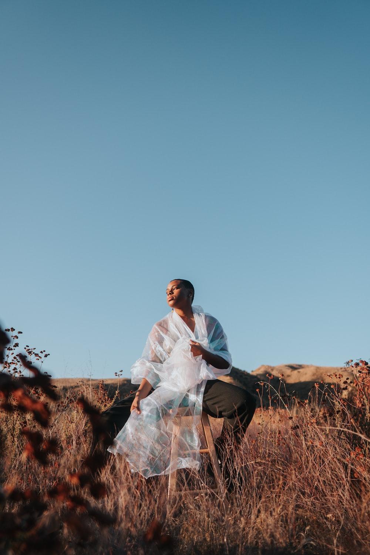 man in white dress shirt sitting on brown rock during daytime