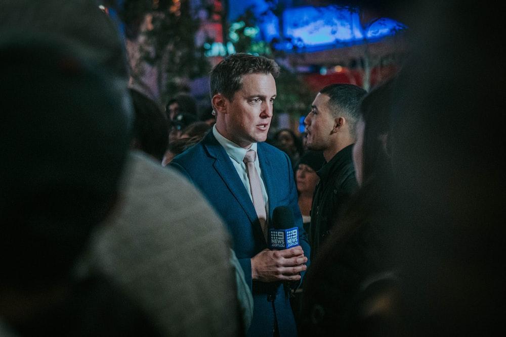 man in black suit standing in front of man in black suit