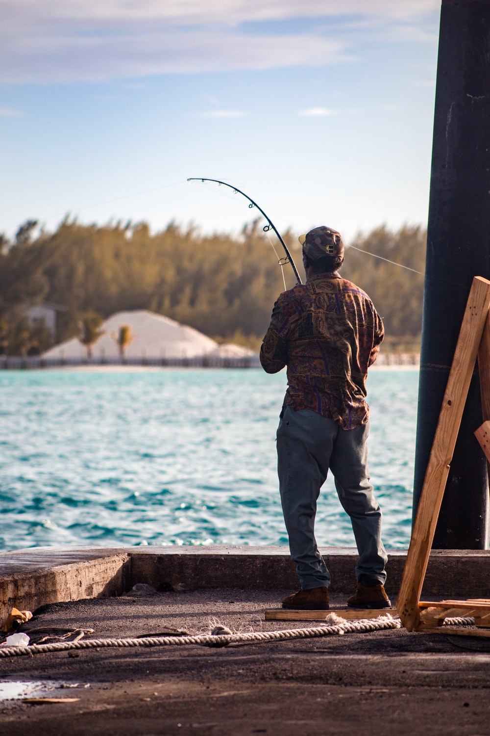 man in brown and black camouflage jacket and blue denim jeans fishing on sea during daytime