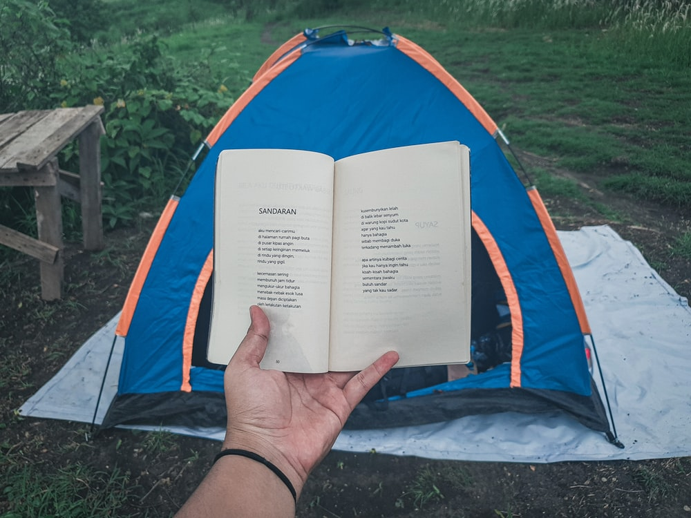 person holding book in blue and orange dome tent