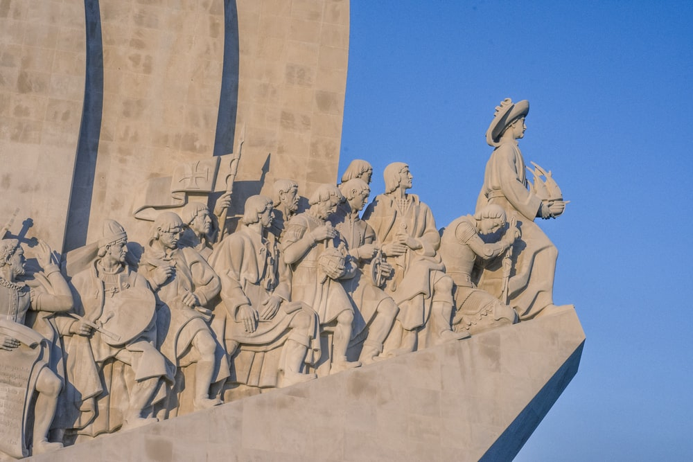 low angle photography of concrete statues under blue sky during daytime