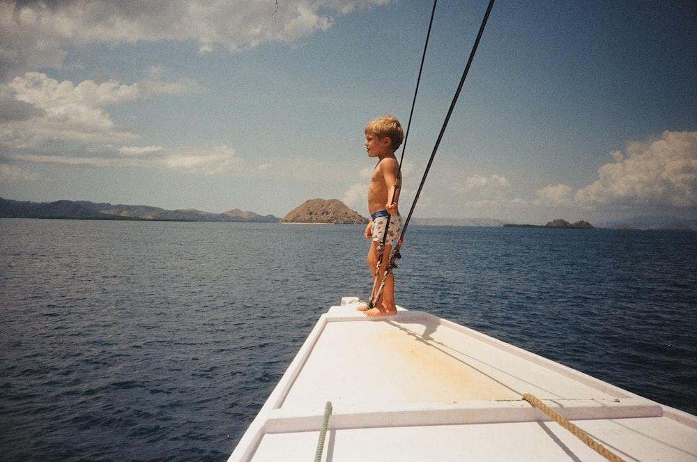 woman in brown bikini sitting on white boat during daytime