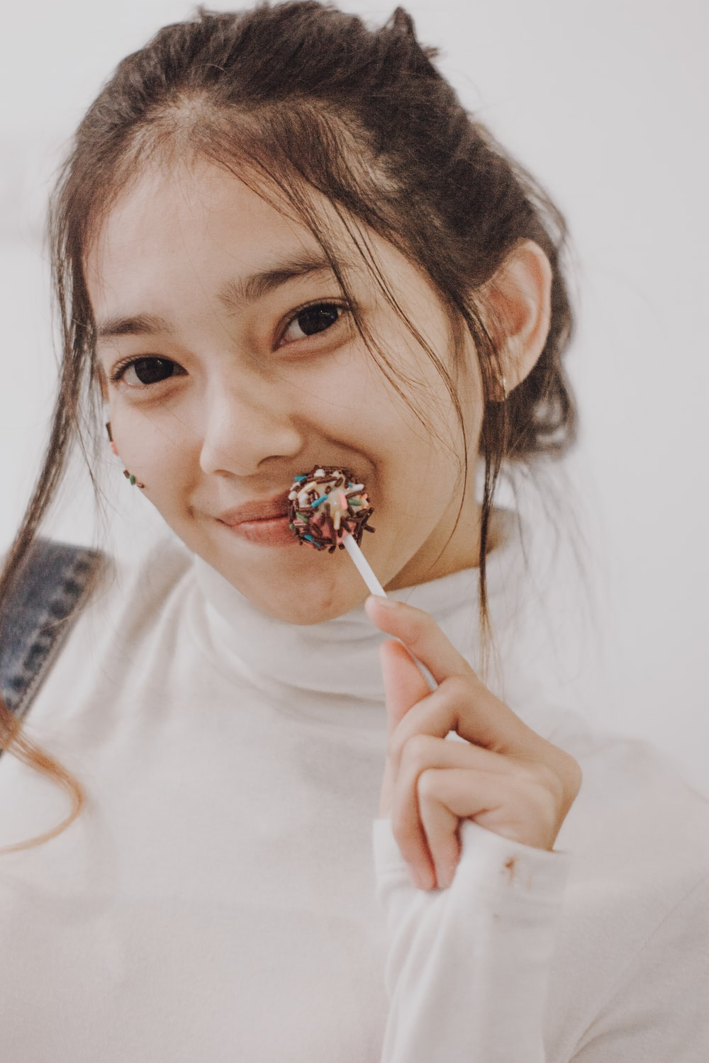 girl in white crew neck shirt holding brown and white lollipop