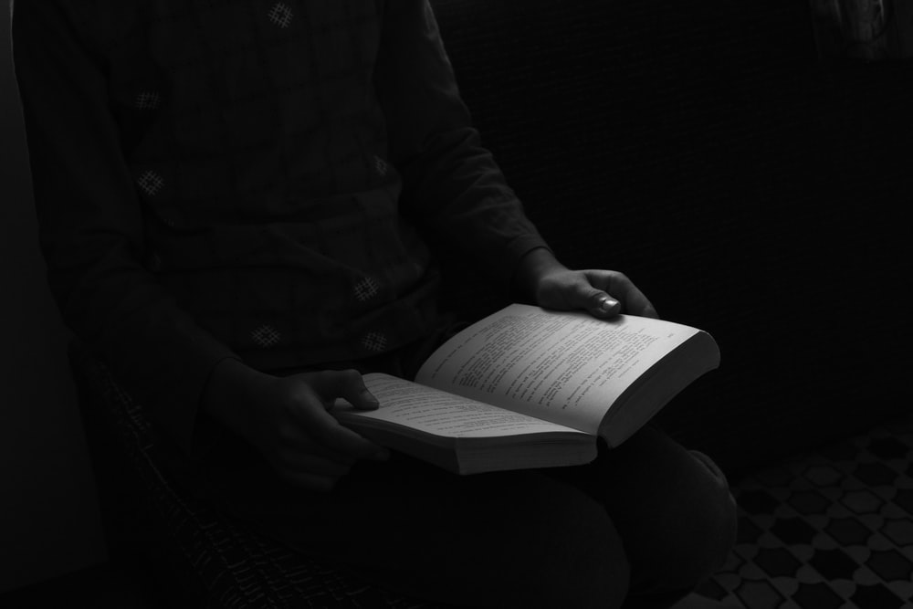 grayscale photo of person reading book