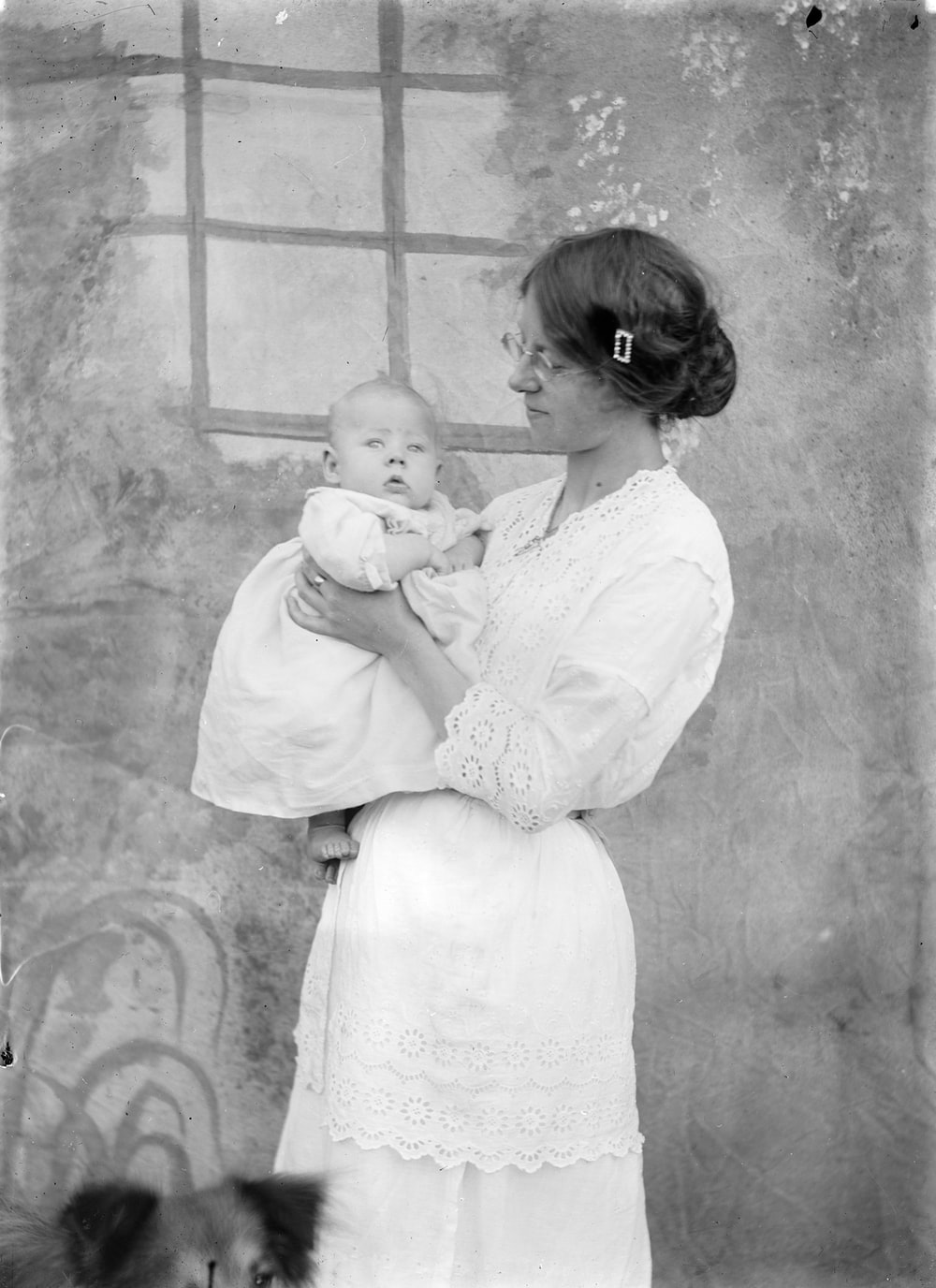 grayscale photo of woman in white dress carrying baby