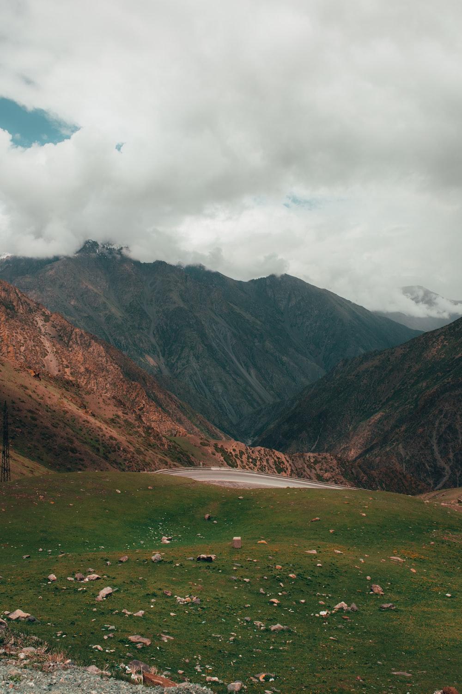 green grass field near brown mountain under white clouds during daytime