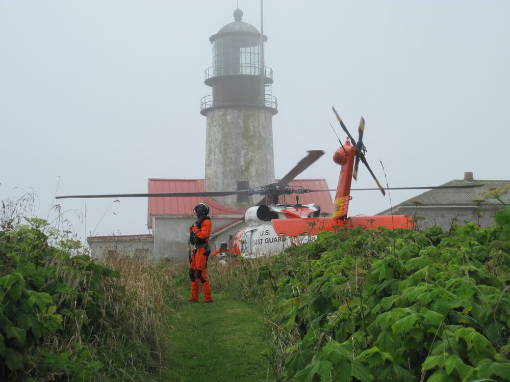 man in white shirt and orange pants standing near white lighthouse during daytime