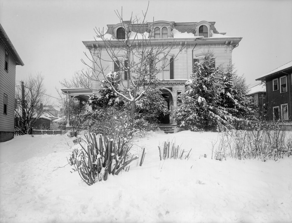 grayscale photo of house covered with snow