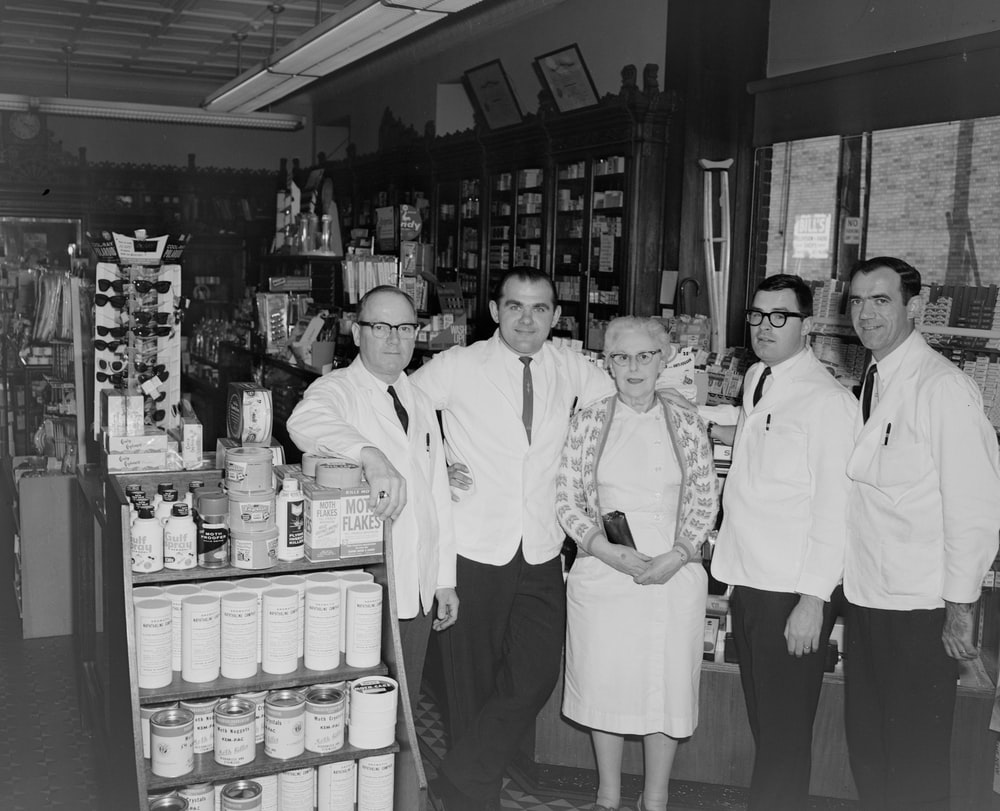 group of men in white uniform standing in front of store