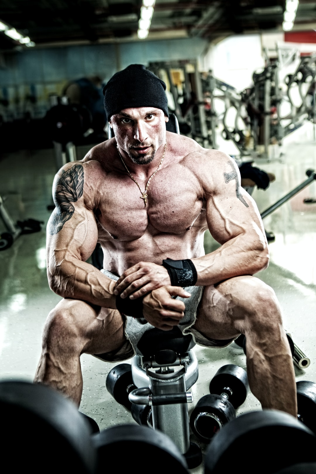 A muscular man in the gym with dumbbells