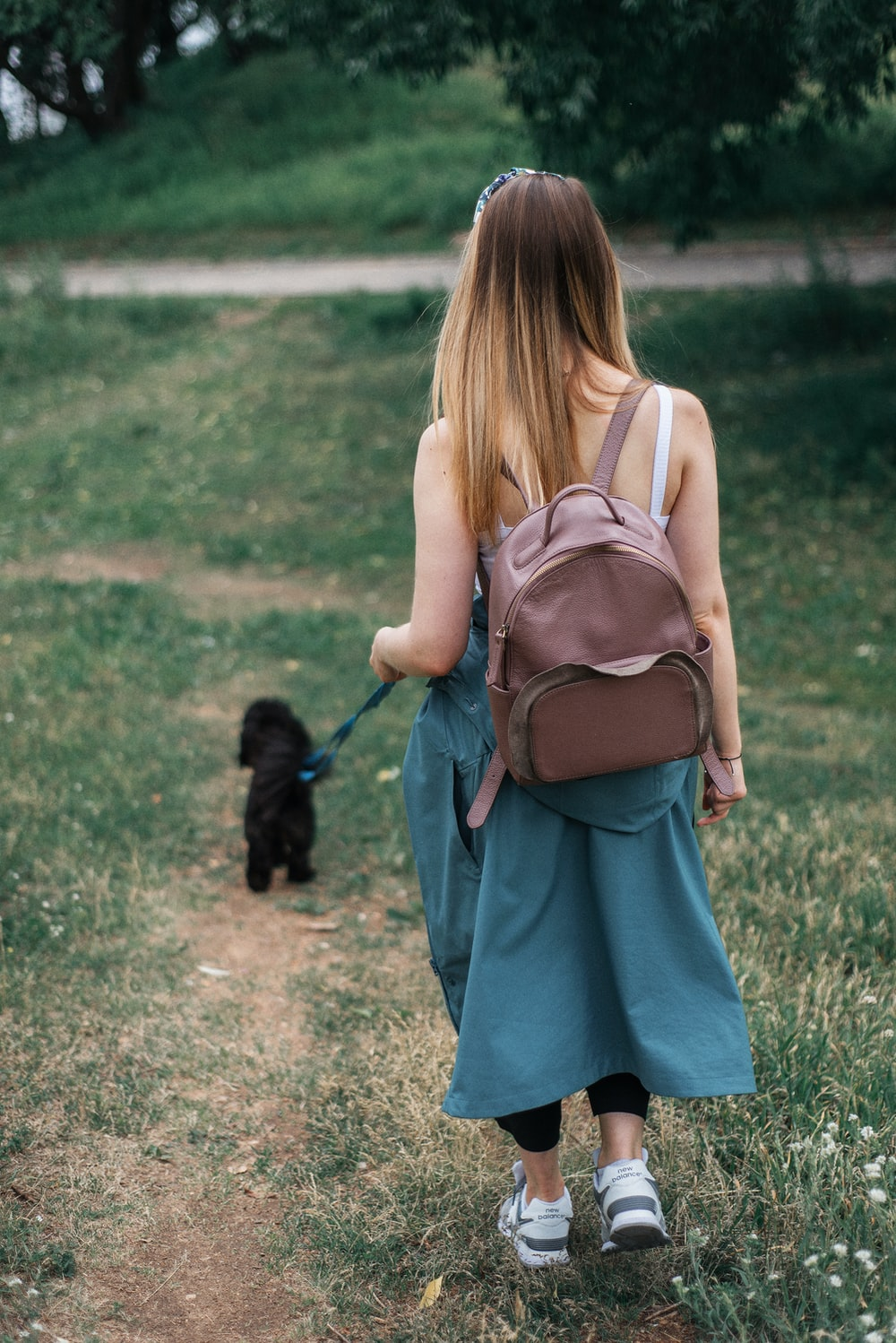 woman in blue dress carrying black dog on green grass field during daytime  photo – Free Strap Image on Unsplash