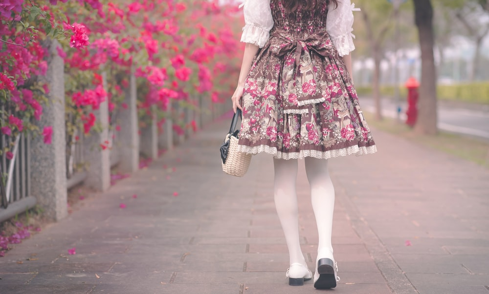 woman in white and pink floral dress walking on sidewalk during daytime