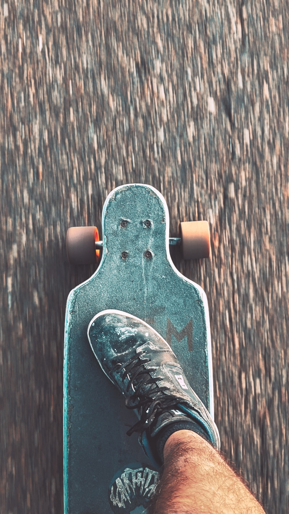 black and white skateboard on brown wooden floor
