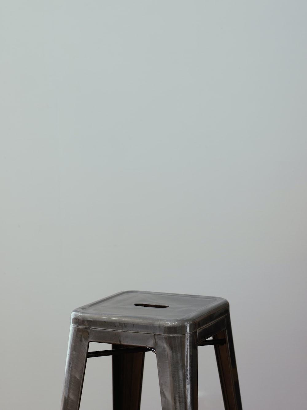 white plastic stool beside white wall