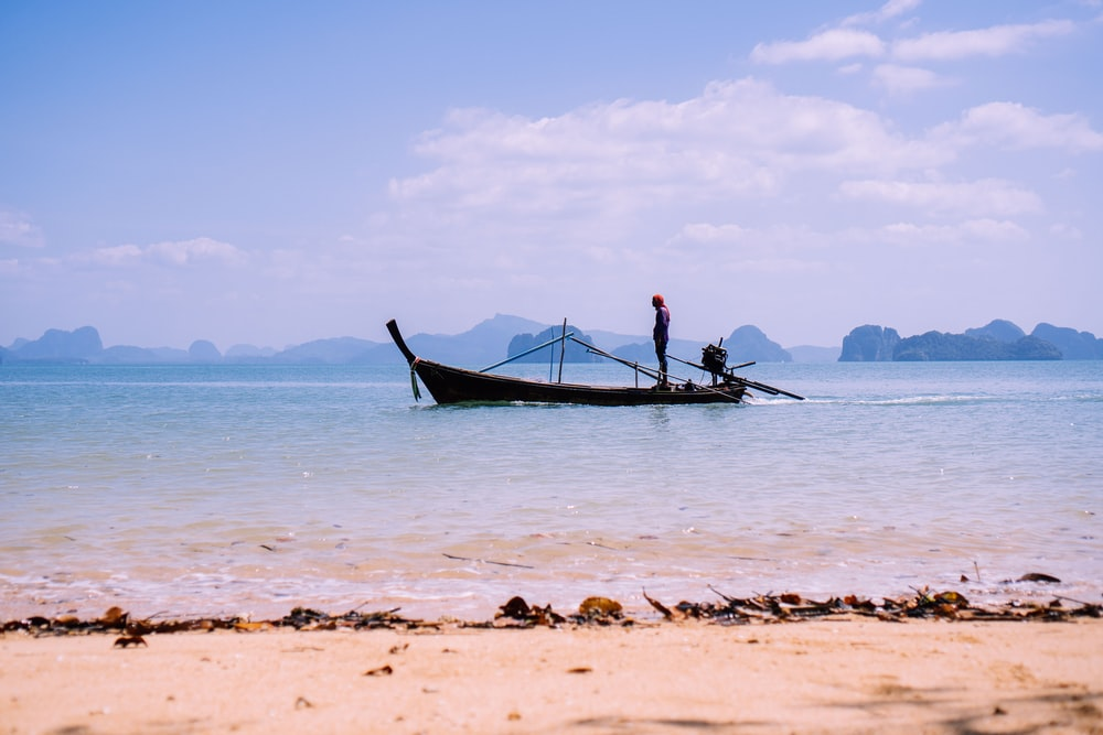 man in black shirt riding on blue boat on sea during daytime