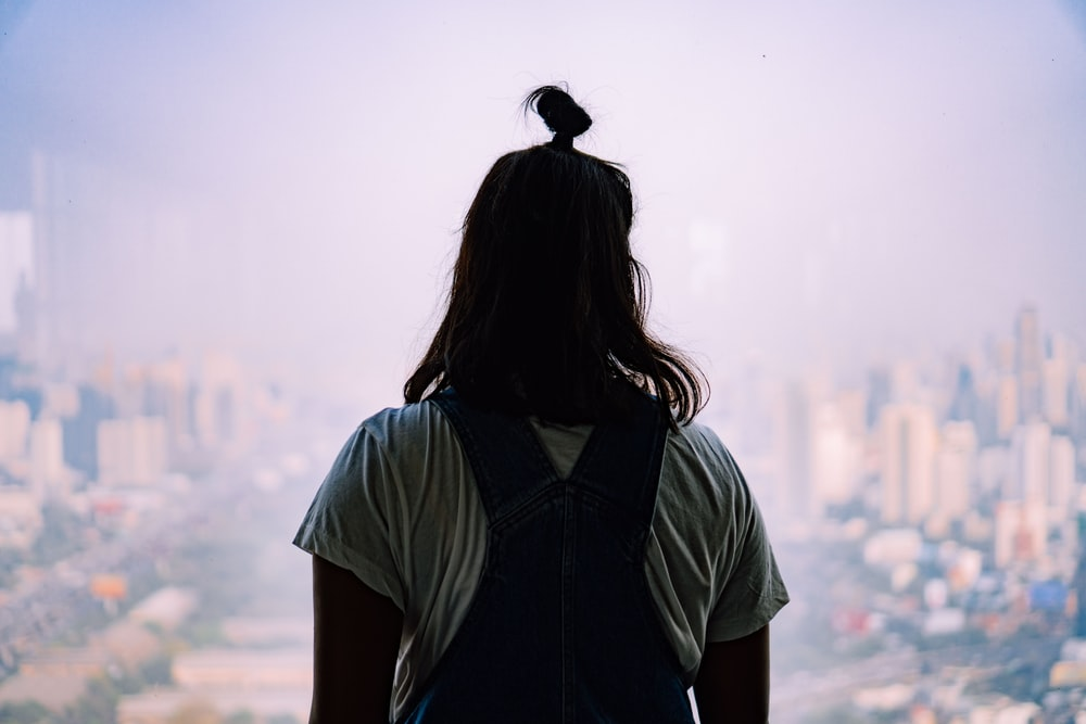 woman in blue shirt standing on top of mountain during daytime