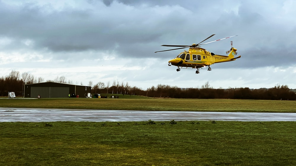 yellow and black helicopter on green grass field under cloudy sky during daytime