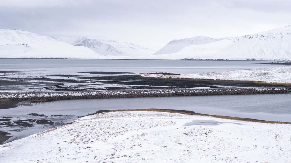 snow covered field near body of water during daytime